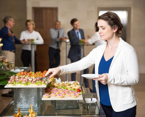 Young businesswoman serving herself with canapes in buffet of restaurant. Business people eating and talking in background