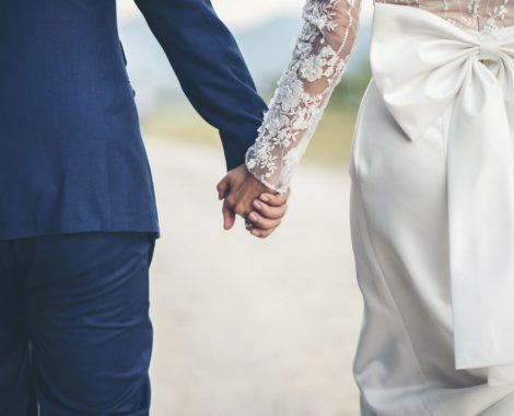 Close up of married couple holding hands in wedding day